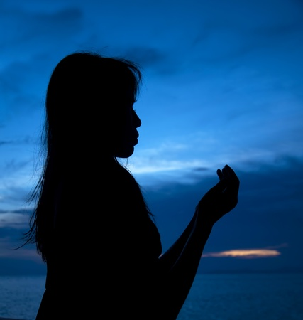 12781842 - silhouette of woman which sits near sea opposite sun and laid down hands before itself and prays